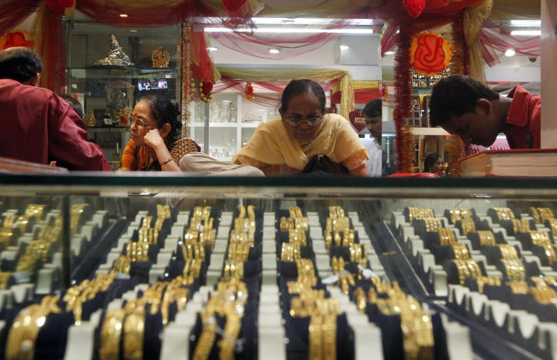 FILE - In this Thursday, Feb. 14, 2013 photo, an Indian woman looks at a display of gold jewelry at a shop in Mumbai, India. As of Monday, April 15, 2013, gold has plunged more than 10 percent the last two days, suggesting that a decade-long surge in the metal is over. Signs that the U.S. economy is healthier are diminishing gold's appeal as an safe place to invest money. Gold peaked at $1,900 in August 2011 and is now at $1,390. (AP Photo/Rajanish Kakade)