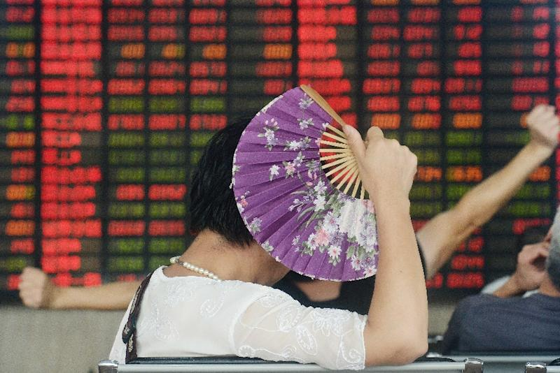An investor holds a fan as she monitors share prices at a securities firm in Shanghai on August 26, 2015