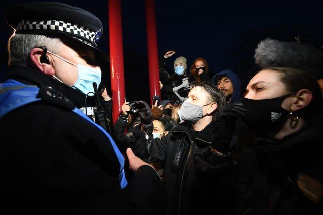 People talk to police as they gathered at the band stand in Clapham Common