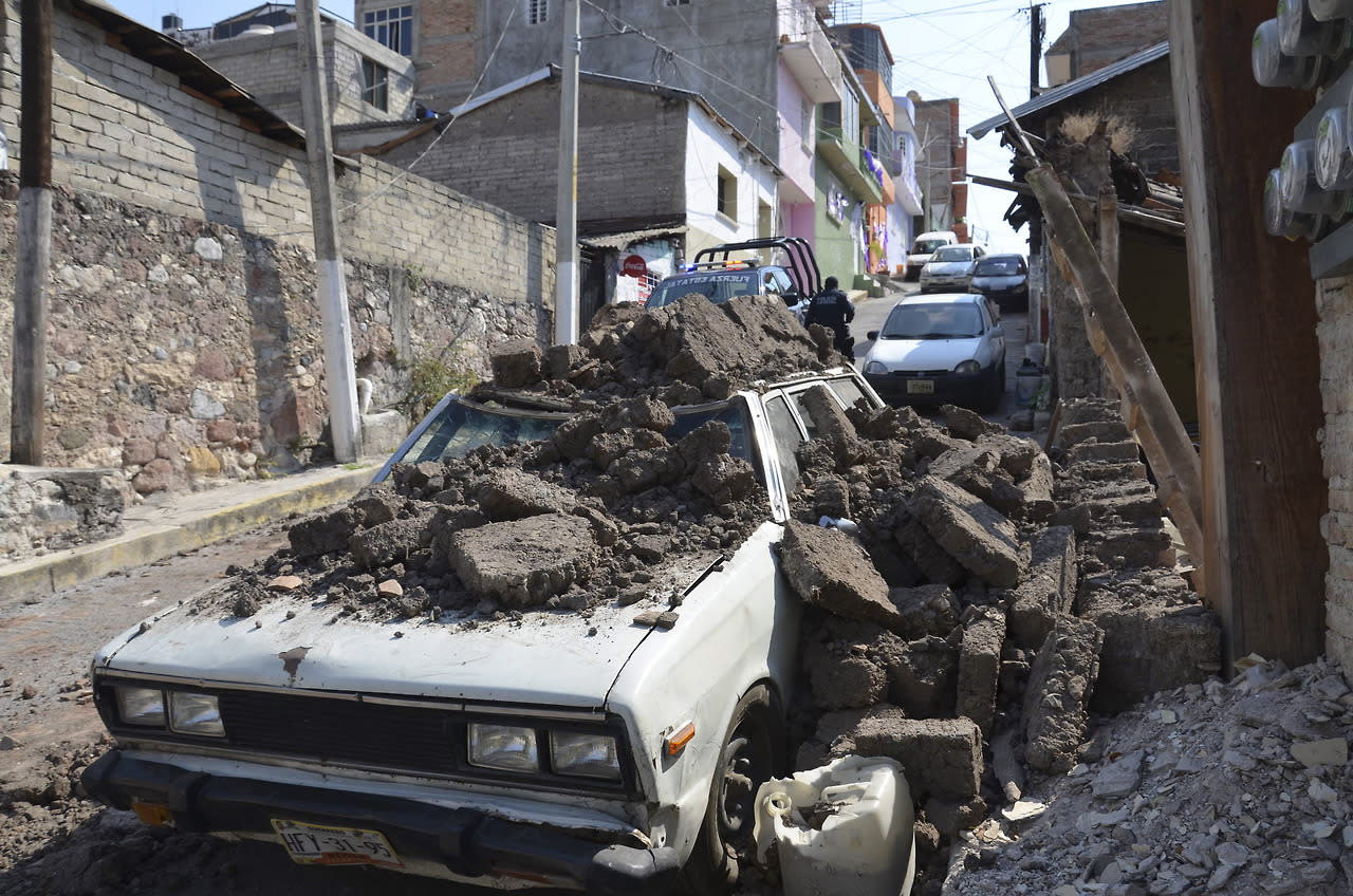 A parked car suffered damage when a adobe wall collapsed on it after a strong earthquake shook Chilpancingo, Mexico, Friday morning, April 18, 2014. (AP Photo/Alejandrino Gonzalez)