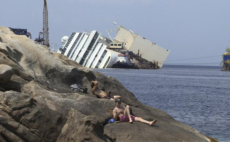In this frame made from APTN video of Monday, July 8, 2013 made available Tuesday July 9, people sunbathe on the rocks as the wreckage of the Costa Concordia cruise ship is seen in the background, on the Tuscan island of Giglio. The trial of the captain of the shipwrecked Costa Concordia cruise liner began Tuesday in a theater converted into a courtroom in Grosseto, Italy, to accommodate all the survivors and relatives of the 32 victims who want to see justice carried out in the 2012 tragedy. The sole defendant, Schettino, made no comment to reporters as he arrived for his trial on charges of multiple manslaughter, abandoning ship and causing the shipwreck near the island of Giglio. His lawyer, Domenico Pepe, told reporters that, as expected, the judge was postponing the hearing though due to an eight-day nationwide lawyers' strike. Schettino has denied wrongdoing. (AP Photo via APTN)