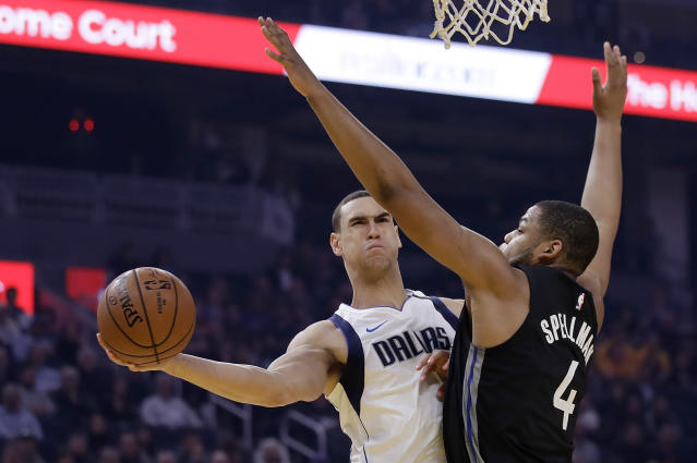 Dallas Mavericks' Dwight Powell, left, passes the ball away from Golden State Warriors' Omari Spellman (4) during the first half of an NBA basketball game Tuesday, Jan. 14, 2020, in San Francisco. (AP Photo/Ben Margot)