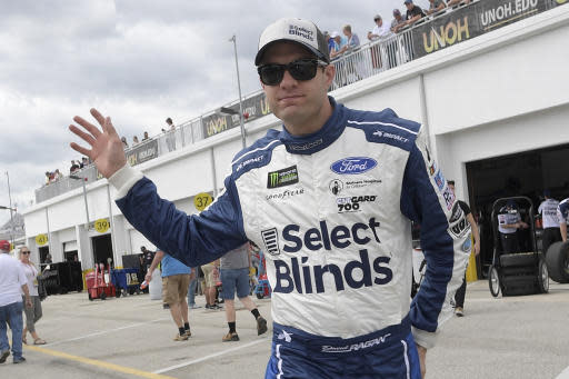 FILE - In this Feb. 16, 2019, file photo, driver David Ragan waves to fans while walking through the garage area during a practice session for the NASCAR Daytona 500 auto race at Daytona International Speedway in Daytona Beach, Fla. David Ragan and Front Row Motorsports announced Wednesday, Aug. 14, 2019, that Ragan will step away from full-time NASCAR competition after this season. Ragan will continue to race on a part-time basis in NASCAR and other series at his desire.(AP Photo/Phelan M. Ebenhack, File)
