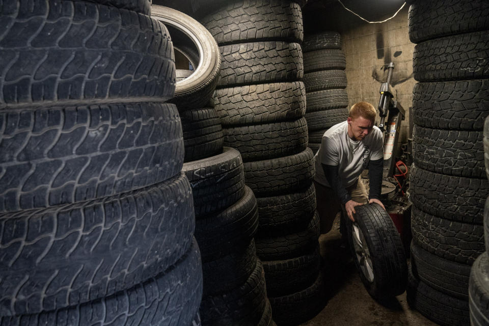 """Steven Ash, 33, works at the tire shop his family owns in Huntington, W.Va., Wednesday, March 17, 2021, and where he overdosed just days before. Ash was 19 when he took his first OxyContin pill and his life spiraled after that. The last year has been particularly brutal. He took more drugs to numb the pain, but it made things worse, a vicious cycle, he said, but he isn't sure how to escape it. He knows he's putting his mother through hell. """"I fight with myself every day. It's like I've got two devils on one shoulder and an angel on the other,"""" he said. """"Who is going to win today?"""" (AP Photo/David Goldman)"""