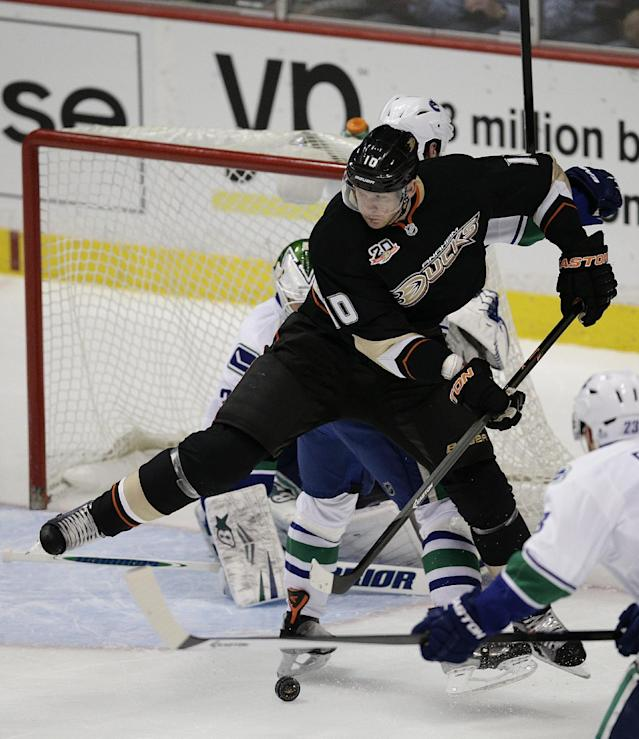 Anaheim Ducks' Corey Perry controls the puck in front of Vancouver Canucks goalie Eddie Lack, of Sweden, during the first period of an NHL hockey game on Wednesday, Jan. 15, 2014, in Anaheim, Calif. (AP Photo/Jae C. Hong)