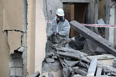 A police sapper inspects a damaged house that was hit by a rocket north of Tel Aviv Israel March 25, 2019. REUTERS/ Ammar Awad