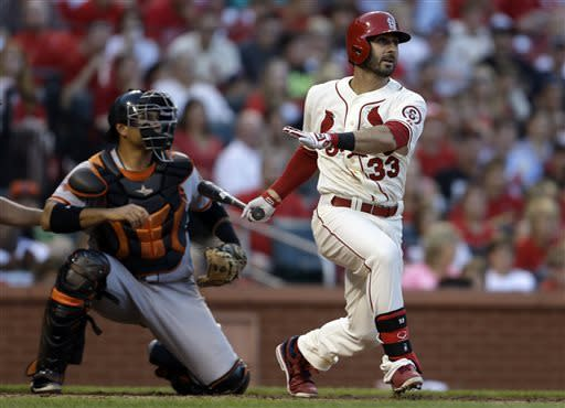 St. Louis Cardinals' Daniel Descalso, right, hits an RBI-single as San Francisco Giants catcher Guillermo Quiroz, left, watches during the sixth inning of the second game of a baseball doubleheader on Saturday, June 1, 2013, in St. Louis. (AP Photo/Jeff Roberson)