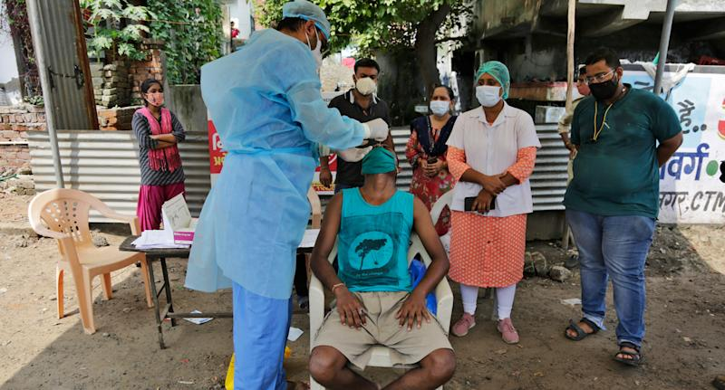 A man is tested for COVID-19 in Ahmedabad on Sunday. Source: AP