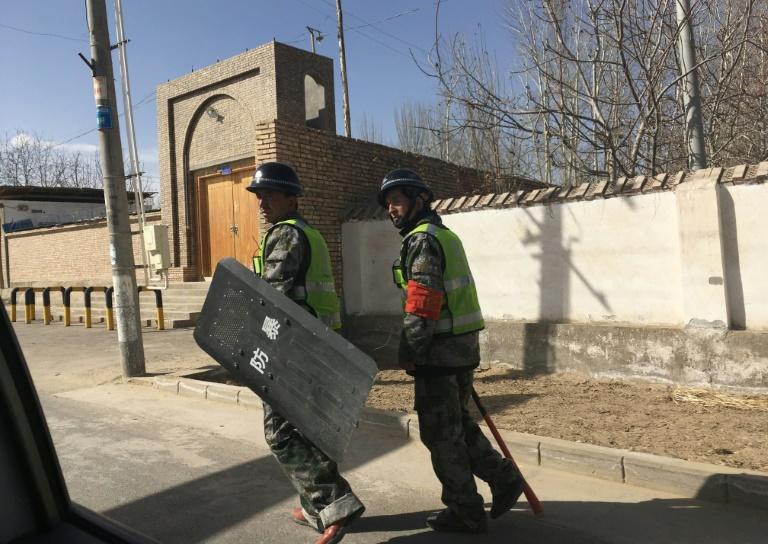 Police patrol a village in Hotan prefecture, in China's western Xinjiang region, where surveillance affects every aspect of daily life