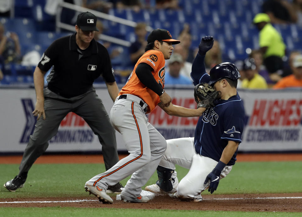 Baltimore Orioles third baseman Rio Ruiz (14) hits Tampa Bay Rays' Ji-Man Choi in the face with his glove after Choi hit a triple off starting pitcher Gabriel Ynoa during the seventh inning of the second baseball game of a doubleheader Tuesday, Sept. 3, 2019, in St. Petersburg, Fla. Choi left the game. Looking on is umpire Ryan Additon. (AP Photo/Chris O'Meara)