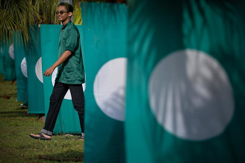 A PAS supporter walks near PAS flags at the 65th Muktamar in Kuantan June 22, 2019. — Picture by Mukhriz Hazim