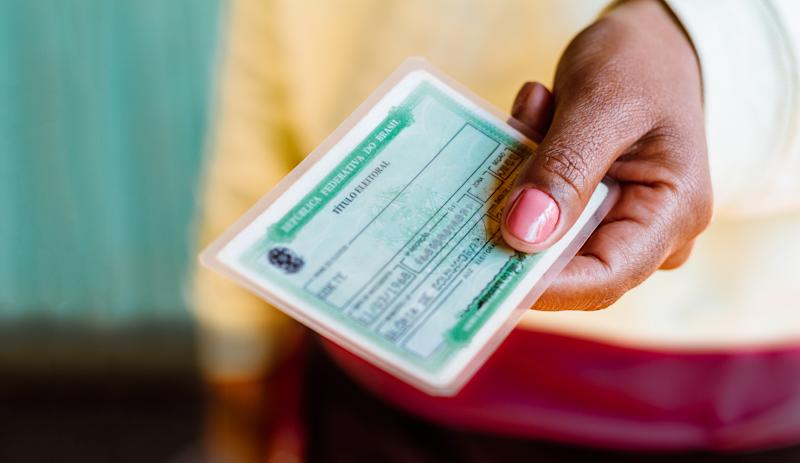 Woman holds the Voter License (Título Eleitoral). It is a document that proves that the person is able to vote in Brazil elections