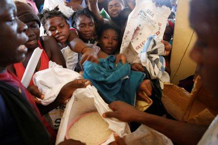 People try to get food during a special distribution in a church after Hurricane Matthew passed through Jeremie, Haiti, October 11, 2016. REUTERS/Carlos Garcia Rawlins