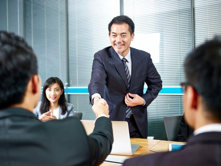 Scene from a Chinese boardroom. Suited executive shakes hands with another businessman as a woman looks on.
