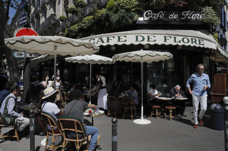 People sit on the Cafe de Flore terrace in Paris, Tuesday, June 2, 2020. Local Parisians are savoring their cafe au lait and croissants at the Left Bank's famed Cafe de Flore, or on the cobbled streets of the ancient Le Marais for the first time in almost three months. As virus confinement measures were relaxed Tuesday, cafes around France were allowed to reopen. (AP Photo/Christophe Ena)