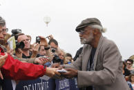 """FILE - U.S. director, actor, and screenwriter Melvin Van Peebles signs autographs for fans during a tribute for his career at the 38th American Film Festival in Deauville, Normandy, France, Wednesday Sept. 5, 2012. Van Peebles, a Broadway playwright, musician and movie director whose work ushered in the """"blaxploitation"""" films of the 1970s, has died at age 89. His family said in a statement that Van Peebles died Tuesday night, Sept. 21, 2021, at his home. (AP Photo/Michel Spingler, File)"""