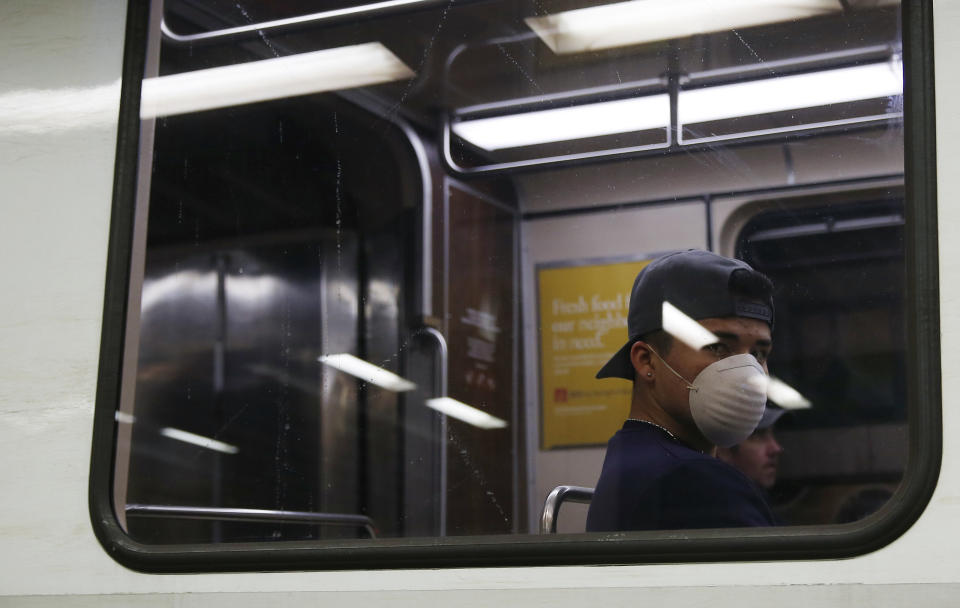 BOSTON, MA - MARCH 25: An MBTA passenger wears a protective face mask as he rides the train at the Government Center T station on March 25, 2020. Gov. Charlie Baker this week issued a stay-at-home advisory for non-essential workers to reduce the spread of coronavirus. (Photo by Jessica Rinaldi/The Boston Globe via Getty Images)