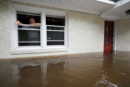 Obrad Gavrilovic peers out the window of his flooded home while considering whether to leave with his wife and pets, as waters rise in Bolivia, North Carolina, U.S., September 15, 2018. REUTERS/Jonathan Drake      TPX IMAGES OF THE DAY