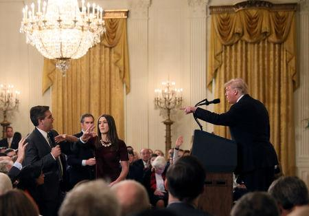 FILE PHOTO: A White House staff member reaches for the microphone held by CNN's Jim Acosta as he questions U.S. President Donald Trump during a news conference in Washington