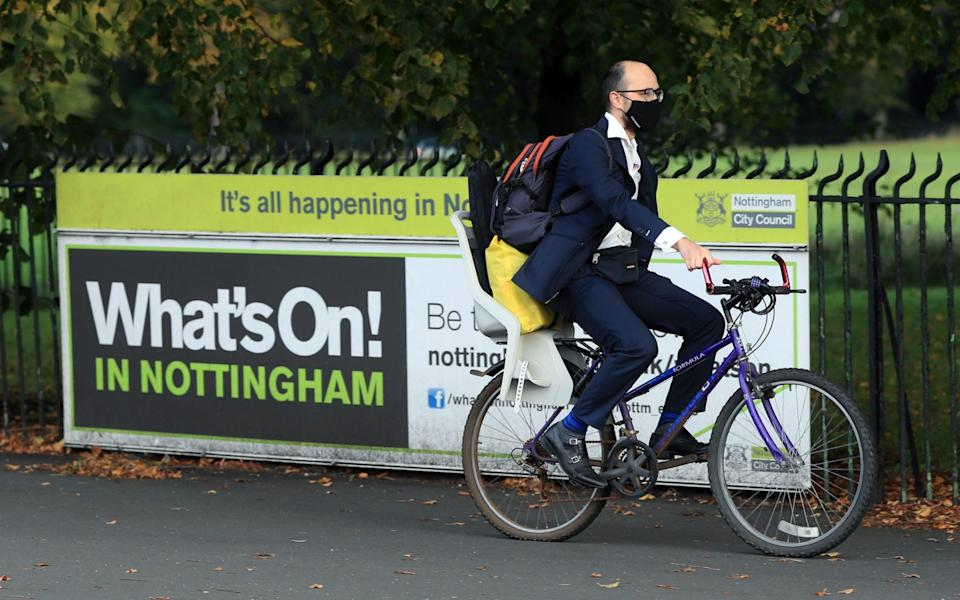 A man wearing a face covering cycling in Nottingham as the city braces itself for a Tier 3 lockdown after a surge in Covid-19 cases - Mike Egerton/PA Wire