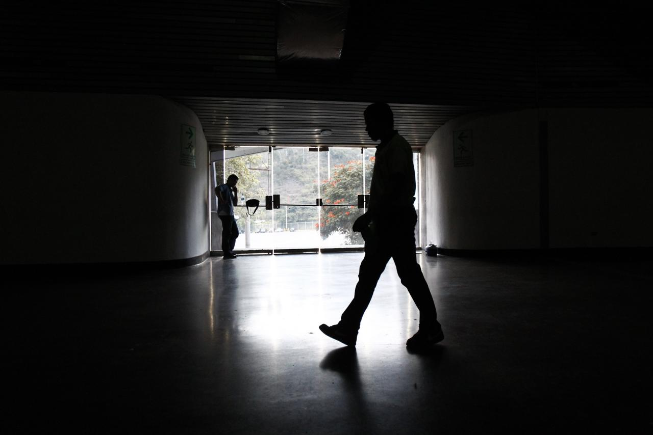 A security guard walks past an exit door as he waits for the power to return after a blackout during the FIBA Americas Championship basketball game between Paraguay and Dominican Republic in Caracas September 3, 2013. A large-scale blackout on Tuesday affected a great part of the capital Caracas and various states of the country, affected locals told Reuters. REUTERS/Carlos Garcia Rawlins (VENEZUELA - Tags: SPORT BASKETBALL ENERGY)