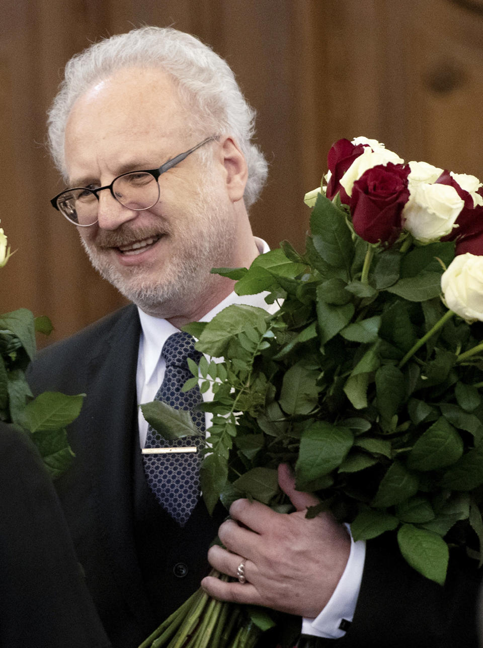 Newly elected Latvian President Egils Levits hold a bunch of flowers after lawmakers elected him in a parliament in Riga, Latvia, Wednesday, May 29, 2019. Levits received 61 votes already in the first round of voting, well above the 51 needed to win the election. (Vladislavs Proskins,/F64 Photo Agency via AP)