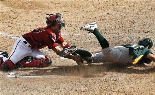 Arizona Diamondbacks' Wil Nieves, left, tags out Oakland Athletics' Adam Rosales who was trying to score in the eighth inning during an MLB spring training baseball game on Friday, March 15, 2013, in Scottsdale, Ariz. (AP Photo/Ross D. Franklin)