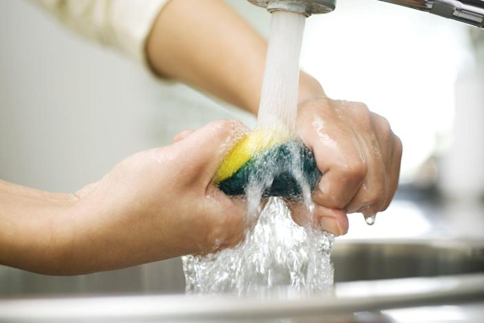 """<p>Though you should replace your kitchen sponge anywhere from once a month to once every two weeks, depending on how much you use it, you can make a sponge last by giving it a good cleaning. However, that old trick of putting a sponge in a microwave probably isn't your best move. </p><p>According to <em>Good Housekeeping</em>, <a href=""""https://www.goodhousekeeping.com/home/cleaning/a18731/how-to-clean-a-sponge/"""" rel=""""nofollow noopener"""" target=""""_blank"""" data-ylk=""""slk:the best way to clean a sponge"""" class=""""link rapid-noclick-resp"""">the best way to clean a sponge</a> is by mixing three quarter cups of bleach in one gallon of water and soaking the sponge for five minutes, then rinsing. </p>"""
