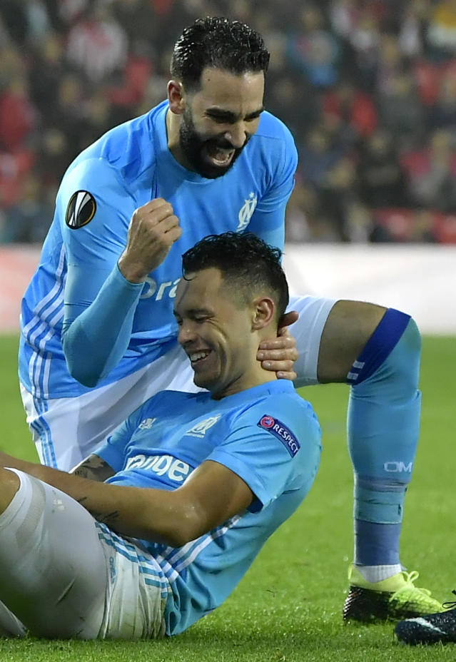 Marseille's Lucas Ocampos, on the pitch, celebrates scoring his team second goal during their Europa League round of 16, 2nd leg, match between Athletic Bilbao and Olympique Marseille, at San Mames stadium, in Bilbao, northern Spain, Thursday, March 15, 2018. (AP Photo/Alvaro Barrientos)