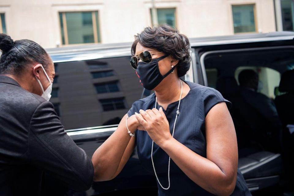 "<p>Washington, D.C.'s Mayor Muriel Bowser watched the procession and exchanged an au courant ""elbow tap"" with another individual. The mayor also chose to wear a black face mask as protection from COVID-19. </p>"