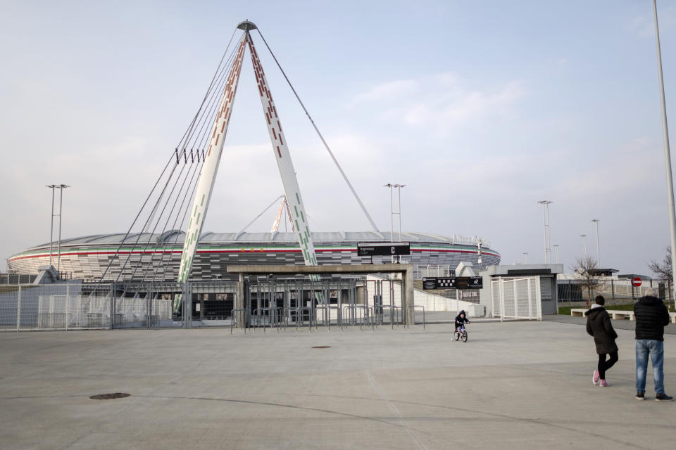 In this picture taken on March 1, 2020 a child rides his bicycle outsited a closed Allianz Stadium in Turin, northern Italy. The Italian Cup semifinal between Juventus and AC Milan scheduled for Wednesday, March 4, 2020 in Turin has been postponed indefinitely as part of measures to stop the spread of the virus outbreak in Italy. (Marco Alpozzi/LaPresse via AP)