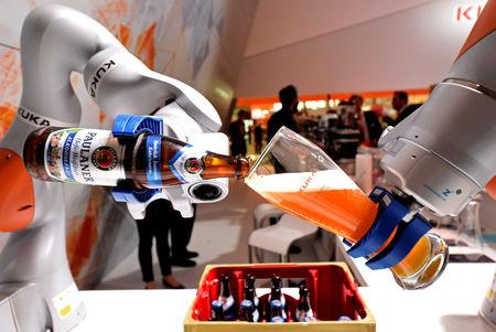 """FILE PHOTO: A robotic arm fills a glass with Bavarian Weiss beer at the booth of German company Kuka at the world's biggest industrial fair, """"Hannover Fair"""", in Hanover, Germany April 24, 2017. REUTERS/Fabian Bimmer/File Photo"""