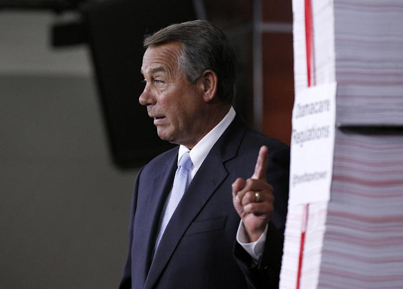 House Speaker John Boehner of Ohio gestures toward a stack of paper representing the 20,000 pages of Affordable Health Care Act regulations during a news conference on Capitol Hill in Washington, Thursday, May 16, 2013. (AP Photo/Molly Riley)