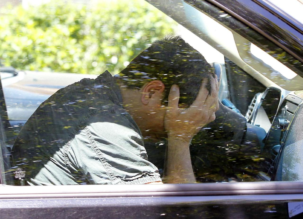 Hugo Mederos, father of shooting victim Amber Nieve Mederos, grandfather of 15-month old victim Lilly, Amber's baby, and ex-husband of victim Lisa Lynn Mederos, sits in a car after speaking outside of the home where five people were gunned down Thursday, May 3, 2012 in Gilbert, Ariz. Police have identified one of the five people killed in a shooting in a Phoenix suburb as a former Marine with ties to new-Nazi and Minutemen groups. (AP Photo/Matt York)