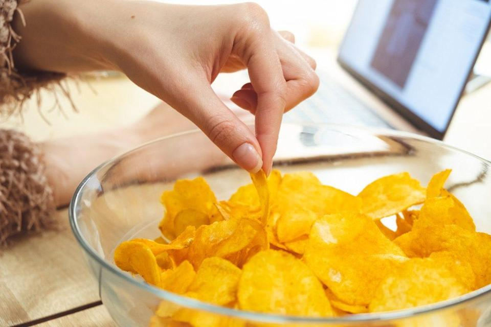 woman in furry sweater reaching into clear glass bowl to grab potato chip while laptop sits in background