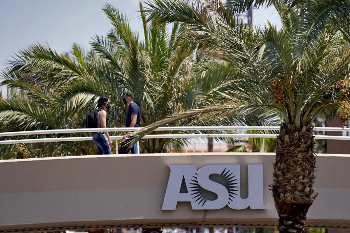 People use a footbridge over University Avenue on the campus of Arizona State University on Tuesday, Sept. 1, 2020, in Tempe, Ariz. Officials in college towns all over the U.S. are fretting that off-campus students are being counted in places other than the communities where their schools are located. (AP Photo/Matt York)