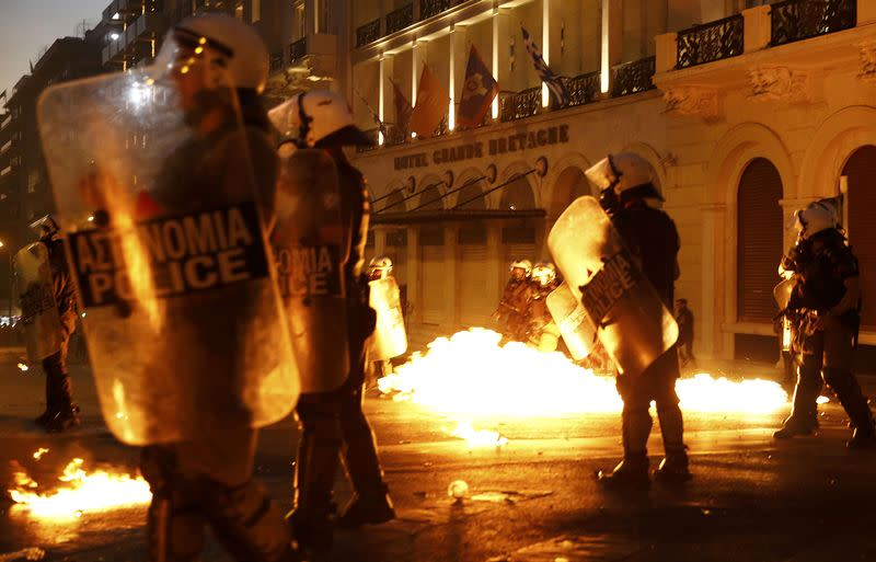 Riot police stand amongst flames from petrol bombs thrown by a small group of anti-austerity demonstrators in Athen