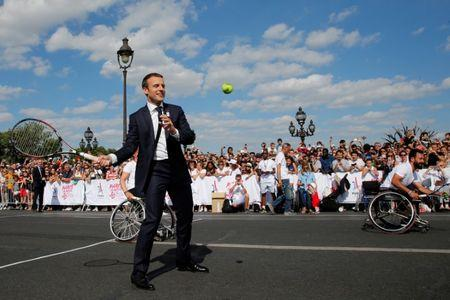 French President Emmanuel Macron plays tennis on the Pont Alexandre III in Paris, France, June 24, 2017. REUTERS/Jean-Paul Pelissier