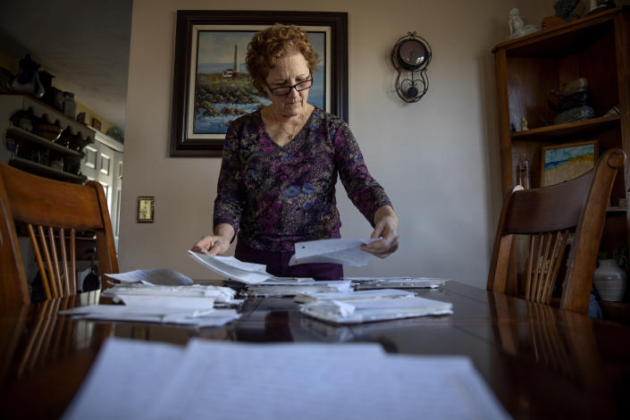"""Janet Uhlar goes through letters she received through her correspondence with imprisoned Boston organized crime boss James """"Whitey"""" Bulger, Friday, Jan. 31, 2020, in Eastham, Mass. During her correspondence and visits with Bulger, Uhlar said, she grew fond of the gangster, though he often warned her that he was a criminal and """"master manipulator."""" When asked if Bulger might have manipulated her, she said, """"I've asked myself that many times. I'll finish reading a letter and say, 'Could he have?' """"(AP Photo/David Goldman)"""