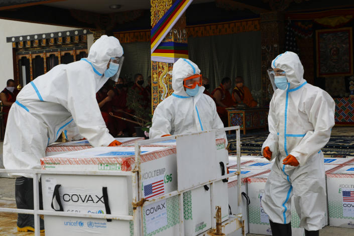 This photograph provided by UNICEF shows airport personnel in protective suit handle unloaded consignment as 500,000 doses of Moderna COVID-19 vaccine gifted from the United States arrived at Paro International Airport in Bhutan, July 12, 2021. The Himalayan kingdom of Bhutan has fully vaccinated 90% of its eligible adult population within just seven days, its health ministry said Tuesday. (UNICEF via AP)
