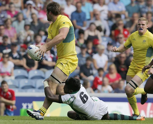 Australia's Liam Gill, left, is stopped by Sri Lanka's Dinusha Chathuranga during the Rugby Sevens Pool D match 1 between Australia and Sri Lanka at the Ibrox stadium during the Commonwealth Games 2014 in Glasgow, Scotland, Saturday July 26, 2014. (AP Photo/Frank Augstein)