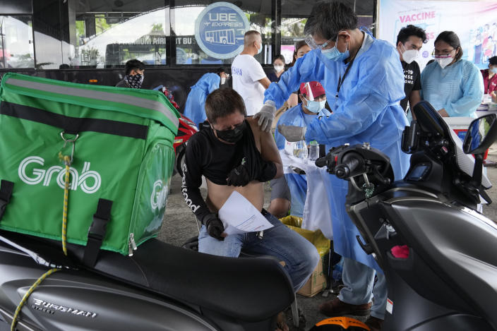 A motorcycle delivery driver is inoculated with China's Sinovac COVID-19 Vaccine at a drive-thru vaccination center in Manila, Philippines, Tuesday, June 22, 2021. The Philippine president has threatened to order the arrest of Filipinos who refuse COVID-19 vaccination and told them to leave the country for hard-hit countries like India and the United States if they would not cooperate with massive efforts to end the pandemic. (AP Photo/Aaron Favila)