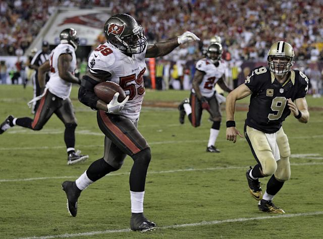 Tampa Bay Buccaneers middle linebacker Mason Foster (59) eludes New Orleans Saints quarterback Drew Brees to score a touchdown on an 85-yard interception return during the fourth quarter of an NFL football game on Sunday, Sept. 15, 2013, in Tampa, Fla. (AP Photo/Chris O'Meara)