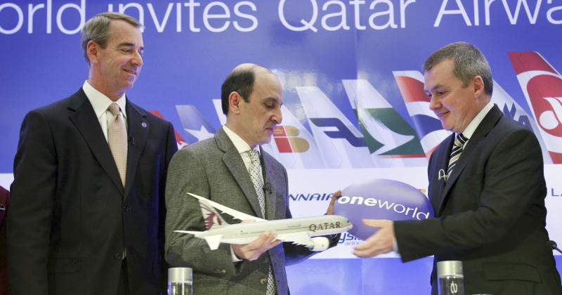 CEO of Qatar Airways Akbar Al Baker, center, exchanges a gift with International Airlines Group chief executive Willie Walsh, right, while American Airlines CEO Tom Horton looks on during a news conference in New York, Monday, Oct. 8, 2012. Qatar Airways is joining an alliance of airlines including American Airlines, British Airways and nine other carriers that coordinate routes and allow passengers to earn frequent flier miles on each other's flights. (AP Photo/Seth Wenig)