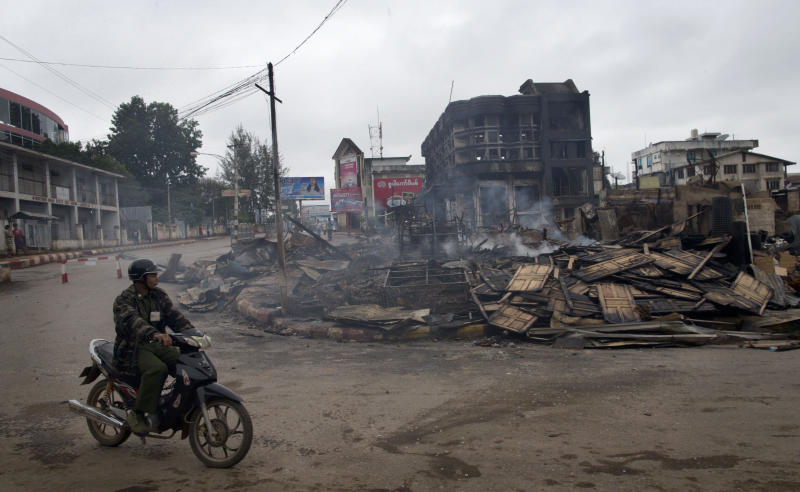 A man rides a motorcycle near a burned building that housed an orphanage for Muslim children in Lashio, northern Shan State, Myanmar, Thursday, May 30, 2013. Many Buddhists and Muslims stayed locked inside their homes and shops were shuttered after two-days of violence in Lashio town, near the border with China, the latest region to fall prey to the country's spreading sectarian violence. (AP Photo/Gemunu Amarasinghe)