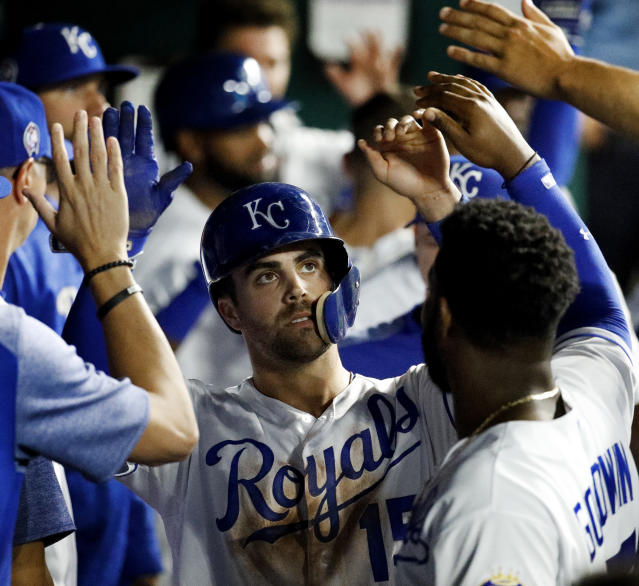 Kansas City Royals' Whit Merrifield celebrates in the dugout after scoring on a sacrifice fly hit by Alex Gordon during the third inning of a baseball game against the Chicago White Sox Tuesday, Sept. 11, 2018, in Kansas City, Mo. (AP Photo/Charlie Riedel)