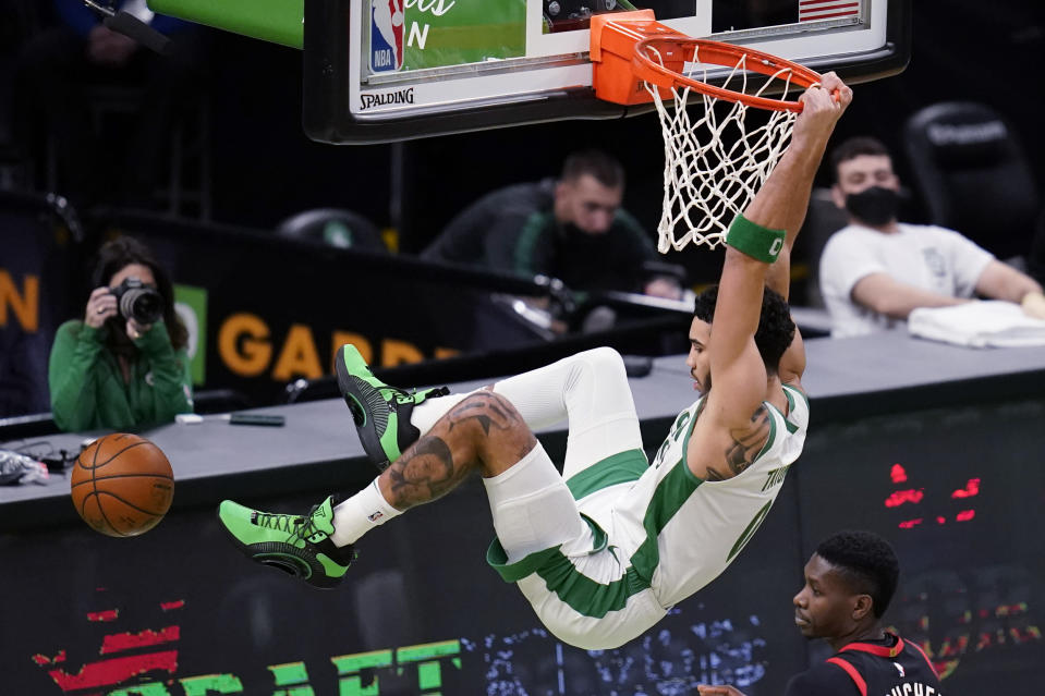 Boston Celtics forward Jayson Tatum (0) hangs on the rim after dunking during the first half of an NBA basketball game against the Toronto Raptors, Thursday, March 4, 2021, in Boston. (AP Photo/Charles Krupa)