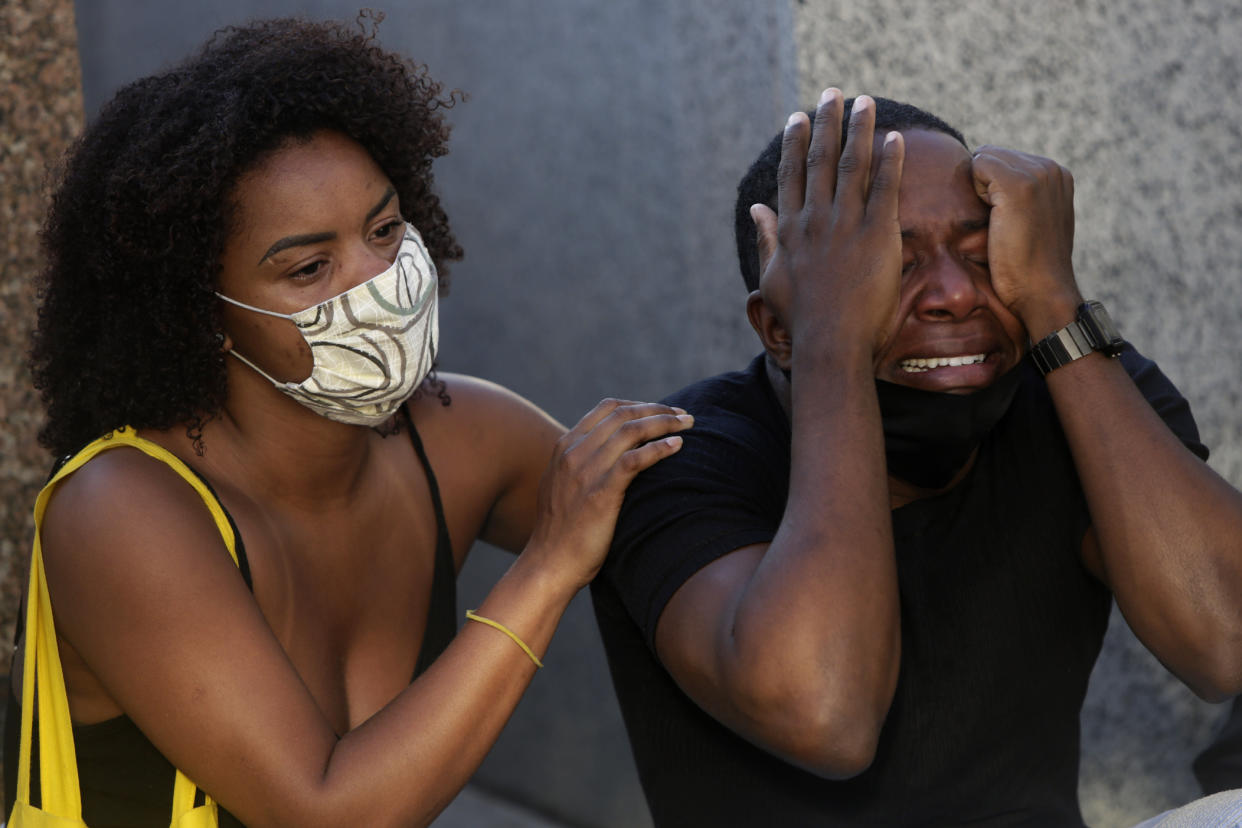 A family member is comforted as he grieves during the burial service of Kathlen Romeu, a young pregnant woman killed by a stray bullet, at a cemetery in Rio de Janeiro, Brazil, Wednesday, June 9, 2021. Stray bullets have struck at least six pregnant women in Rio since 2017, but Romeu was the first to die, according to Crossfire, a non-governmental data project that tracks armed violence. (AP Photo/Bruna Prado)