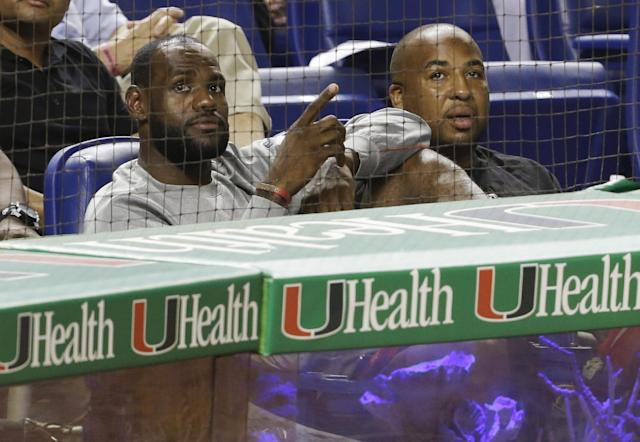 Miami Heat's LeBron James, left, sits behind home plate during a baseball game between the Miami Marlins and the Los Angeles Dodgers, Wednesday, Aug. 21, 2013, in Miami. (AP Photo/Lynne Sladky)