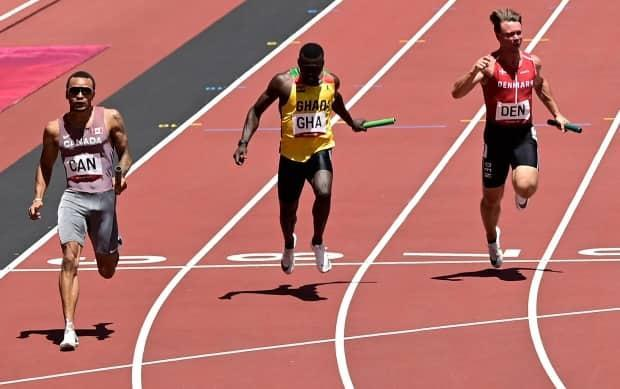 Canada's Andre De Grasse crosses the finish line in second place ahead of Ghana's Joseph Paul Amoah, middle, and Denmark's Frederik Schou Nielsen in the men's 4x100-metre relay heats at the Tokyo Olympics on Thursday in Japan. (Javier Soriano/AFP via Getty Images - image credit)